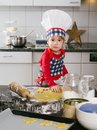 Young boy making cookies photo of an adorable in a chef hat and apron snowflake in the kitchen Royalty Free Stock Photography