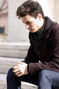 Young boy man thinking about his problems a is concept of stress youth the is wearing a dark coat a scarf and blue jeans Royalty Free Stock Photo