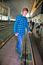 Young boy on a moving staircase inside the airport Royalty Free Stock Photo