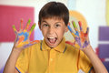 Young boy with painted hands expressing joy in art room Royalty Free Stock Images