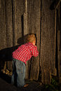 Young boy peeks inside barn a farmer a Stock Image