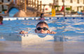 Young boy peering out of a swimming pool wearing sunglasses goggles camera supports himself paving surround with his hands hot Royalty Free Stock Photos