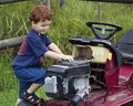 Young boy playing with broken lawnmower Stock Images