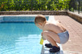 Young boy playing at the edge of a swimming pool Royalty Free Stock Photo