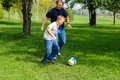 Young boy playing football with his father Royalty Free Stock Photos