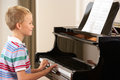 Young boy playing grand piano Royalty Free Stock Photo