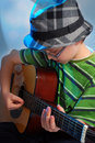 Young boy playing guitar in hat the classical on stage Royalty Free Stock Photo