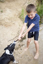 Young boy playing with his dog at the river a stick Royalty Free Stock Images