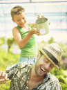 Young boy playing with his father in a green house happy Stock Photos