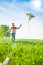 Young boy playing with his kite in a green field flies an open little kid on meadow childhood concept Royalty Free Stock Photography