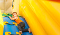 Young boy playing in an inflatable slide blond trying to climb it Royalty Free Stock Images