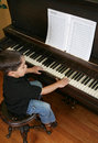 Young boy playing piano Stock Images