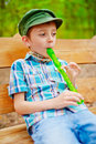Young boy playing recorder stylish kid plays on green Stock Photos