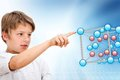 Young boy pointing at 3D molecules. Royalty Free Stock Photos