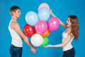 Young boy presenting baloons to girl over blue background Stock Photos
