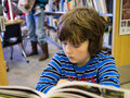 Young boy reading a book in a public library Royalty Free Stock Photo