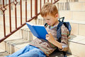 Young boy is reading book on school stairs Stock Photo