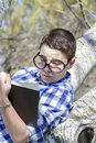 Young boy reading a book in the woods with shallow depth of fiel field and copy space Stock Image