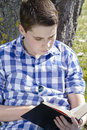 Young boy reading a book in the woods with shallow depth of fiel field and copy space Royalty Free Stock Photos
