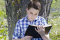 Young boy reading a book in the woods with shallow depth of fiel field and copy space Stock Photos