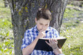 Young boy reading a book in the woods with shallow depth of fiel field and copy space Stock Photo