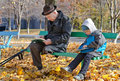 Young boy reading with his grandfather disabled as they sit side by side on a bench in the park on a chilly autumn day enjoying Stock Photos
