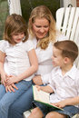 Young Boy Reads to His Mother and Sister Royalty Free Stock Images