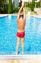 Young boy is ready for dive a to jump into swimming pool Stock Photo