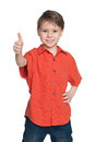Young boy in the red shirt holds his thumb up on white background Royalty Free Stock Images