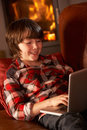 Young Boy Relaxing With Laptop By Cosy Log Fire Royalty Free Stock Image