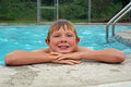Young boy resting after swimming a youngboy by the pool with a broad smile and look of delight on his face rest beside the pool i Royalty Free Stock Photos