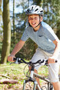 Young boy riding bike along country track in the sun having fun Stock Photo
