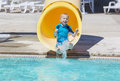 Young boy riding down a yellow water slide cute at an outdoor waterpark Stock Photography
