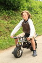 Young boy riding small motorbike smiling in grey clothes on asphalt road Stock Photo