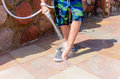 Young boy rinsing beach sand off his legs and shoes with a hose pipe at a seaside resort on summer vacation Royalty Free Stock Photos