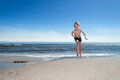 Young boy running along the beach in his swimsuit on a sunny summer day coming towards camera with ocean at his back with Royalty Free Stock Photos