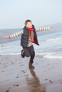 Young Boy Running Along Winter Beach Royalty Free Stock Photo