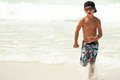 Young Boy Running in Ocean Stock Photo