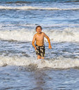 Young boy running through the water at the beach happy Royalty Free Stock Photography