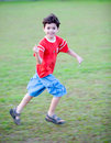 Young boy runs as he pulls the string of his kite Royalty Free Stock Images