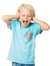 Young boy screams and covers ears Stock Photo
