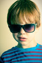 Young boy with shades a cross processed image of a wearing Royalty Free Stock Photography