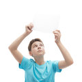 Young boy with a sheet of paper in cyan t shirt holding an empty copyspace over his head composition isolated over the white Stock Photo