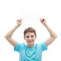Young boy with a sheet of paper in cyan t shirt holding an empty copyspace over his head composition isolated over the white Royalty Free Stock Photos