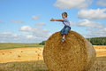 Young boy sitting on haystack in the field smiling and pointing his hands aside as if calling to have fun with him Stock Images