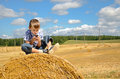 Young boy sitting on haystack with phone in the field and playing his Stock Photo