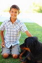 A young boy sitting with his pet dog outdoors Royalty Free Stock Photo
