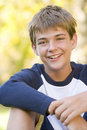 Young boy sitting outdoors smiling Stock Image
