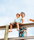Young boy sitting on a railing with his father Stock Image