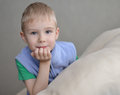 Young boy sitting on sofa looking at camera gray background Royalty Free Stock Images